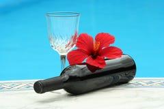 Un vidrio de vino rojo por la piscina foto de archivo libre de regalías
