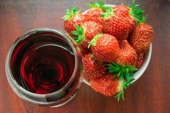 Un vidrio de vino rojo y de fresas Imagen de archivo