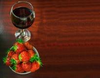 Un vidrio de vino rojo y de fresas Fotos de archivo