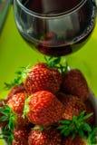 Un vidrio de vino rojo y de fresas frescas Imagen de archivo libre de regalías
