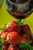 Un vidrio de vino rojo y de fresas frescas Fotos de archivo