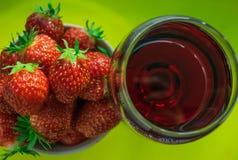 Un vidrio de vino rojo y de fresas frescas Foto de archivo
