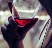 Un vidrio de vino tinto en las manos de una muchacha imagenes de archivo