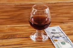 Un vidrio de vino tinto y de dólares fotos de archivo