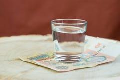 Un vidrio de vodka en un corte de madera presionó la vieja rublo soviética, pagada una bebida Fotografía de archivo libre de regalías