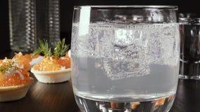 Un vidrio de vodka en la tabla con un bocado metrajes
