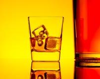 Un vidrio de whisky con los cubos de hielo cerca de la botella en la tabla con la reflexión, atmósfera amarilla caliente del tint Imagen de archivo