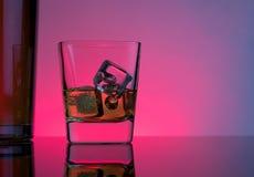Un vidrio de whisky con los cubos de hielo cerca de la botella en la tabla con la reflexión, atmósfera del disco de las luces Fotografía de archivo