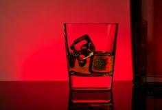 Un vidrio de whisky con los cubos de hielo cerca de la botella en la tabla con la reflexión, atmósfera del disco de las luces roj Imágenes de archivo libres de regalías