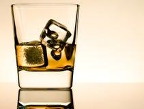 Un vidrio de whisky con los cubos de hielo en la tabla con la reflexión, atmósfera marrón clara Imagen de archivo libre de regalías