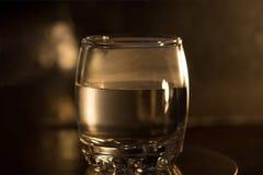 Un vidrio de whisky con una botella en el fondo Fotografía de archivo libre de regalías