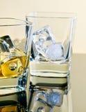 Un vidrio de whisky y uno vacíos con los cubos de hielo en la tabla con la reflexión Foto de archivo libre de regalías