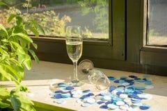 Un vidrio del champán con champán en el alféizar foto de archivo libre de regalías