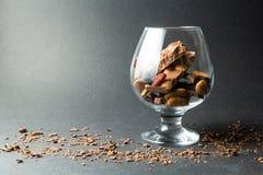 Un vidrio del chocolate en un fondo negro, migas del chocolate Espacio para el texto foto de archivo libre de regalías