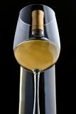 Un vidrio del vino blanco y de la botella de vino Foto de archivo libre de regalías