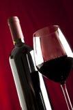 Un vidrio del vino rojo y de una botella Imagenes de archivo