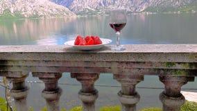 Un vidrio del vino rojo y de una placa de fresas brillantes en el balcón con las montañas en el fondo Fotos de archivo