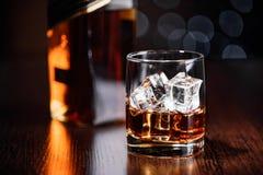 Un vidrio del whisky en las rocas y de una botella en la tabla Imagen de archivo