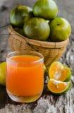 Un vidrio del zumo y de la cesta de naranja en fondo de madera. Imagenes de archivo
