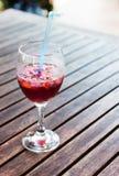 Un vidrio semilleno de cristal de sangría y de hielo. Fotos de archivo