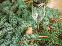 Un vidrio vacío de champán y del corcho está en el fondo de las ramas del abeto, fondo de la Navidad Imagenes de archivo