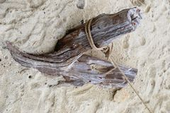 Un vieil accroc sur le sable attaché avec une corde photo stock