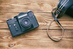Un vieil appareil-photo sur une table faite de conseils texturisés foncés photos libres de droits