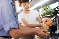 Un vieil homme et un garçon lavent des légumes Le vieil homme lave les feuilles de la salade, les lavages de garçon la tomate Images libres de droits