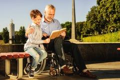 Un vieil homme montre quelque chose à son petit-fils dans un livre Le vieil homme s'assied sur un fauteuil roulant Image stock