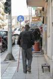 Un vieil homme plus âgé dans un chapeau noir de chemise et marche avec une canne sur la rue de la ville grecque de Kavala La Gr image stock