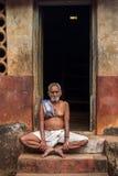 Un vieil homme s'asseyant sur les étapes de sa maison Photos stock