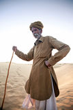 Un vieil homme se tenant sur une dune, vivant dans le désert, un conducteur de chameau Photographie stock