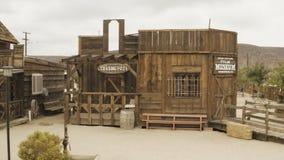Un vieil ouest sauvage regardant des bâtiments avec une antenne tirent vers le haut au désert à l'arrière-plan banque de vidéos