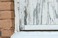 Un viejo blanco pintó la ventana de donde está el chiping la pintura Fotos de archivo libres de regalías