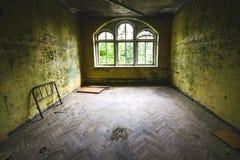 Un viejo cuarto con las ventanas destruidas en un lugar abandonado fotos de archivo