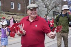 Un viejo hombre en camiseta roja distribuye Canadá 150 banderas a la gente Foto de archivo