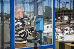 Un viejo hombre está llamando de un teléfono público imagenes de archivo