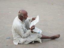 Un viejo hombre pobre que lee un periódico Foto de archivo libre de regalías