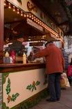 Un viejo hombre que compra un poco de comida en un mercado de la Navidad en Göttingen, Alemania fotos de archivo
