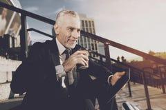 Un viejo hombre respetable en un traje de negocios estricto se sienta en pasos de la oficina Él trabaja en una tableta, al lado d Fotografía de archivo