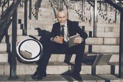 Un viejo hombre respetable en un traje de negocios estricto se sienta en pasos de la oficina Él trabaja en una tableta, al lado d Fotos de archivo libres de regalías