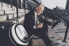 Un viejo hombre respetable en un traje de negocios estricto se sienta en pasos de la oficina Él trabaja en una tableta, al lado d Fotos de archivo