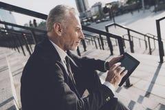 Un viejo hombre respetable en un traje de negocios estricto se sienta en pasos de la oficina Él trabaja en una tableta, al lado d Imagenes de archivo