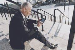 Un viejo hombre respetable en un traje de negocios estricto se sienta en pasos de la oficina Él trabaja en una tableta, al lado d Foto de archivo libre de regalías