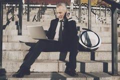 Un viejo hombre respetable en un traje de negocios estricto se sienta en pasos de la oficina Él trabaja en una tableta, al lado d Foto de archivo