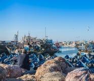 Un viejo hombre se sienta en las miradas de la jábega en los barcos azules en Skala du Fotos de archivo libres de regalías