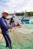 Un viejo pescador está quitando las anchoas pesca de su red de pesca para comenzar un nuevo día laborable en la isla del hijo de  Foto de archivo libre de regalías