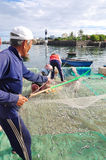 Un viejo pescador está quitando las anchoas pesca de su red de pesca para comenzar un nuevo día laborable en la isla del hijo de  Imagen de archivo libre de regalías