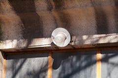 Un viejo una solas bombilla y lámpara al aire libre en la puerta de la pared delantera de la casa, primer Fotos de archivo libres de regalías