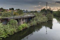 Un vieux, abandonné, établissant, près d'un canal calme, envahi avec le feuillage, l'ensemble dans une terre en friche urbaine Photos libres de droits